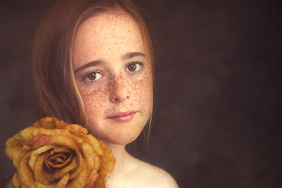 Portrait of a young girl with freckles and red hair