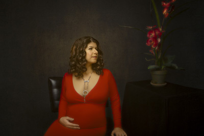 Maternity art portrait of woman in red dress